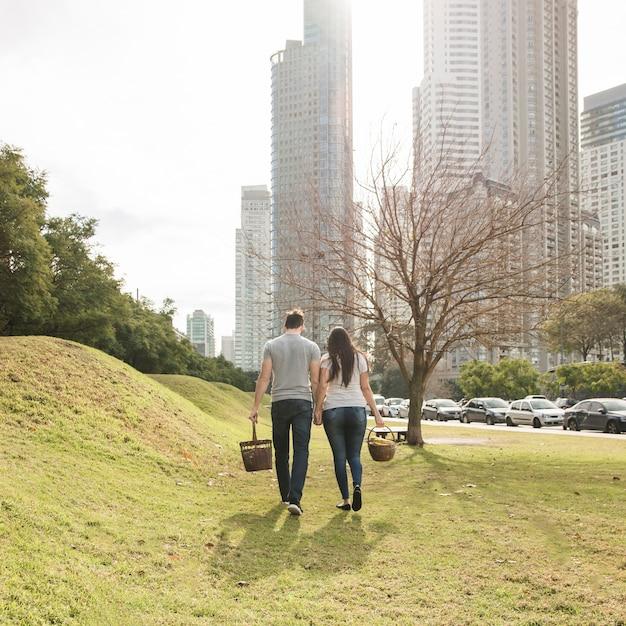 Achtermening van jong paar die dichtbij het stadspark lopen Gratis Foto