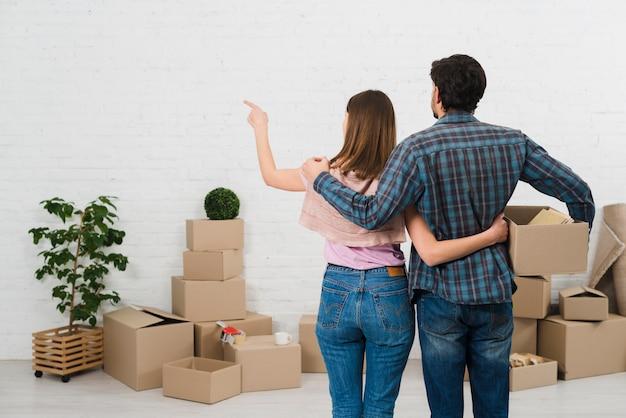 Achtermening van jong paar die zich voor kartondozen bevinden die geschilderde witte muur bekijken Gratis Foto