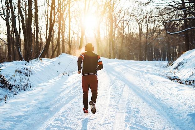 Achtermening van jonge atletische agent in sportkleding met hoofdtelefoons die in het winterse bos in de ochtend lopen. Premium Foto