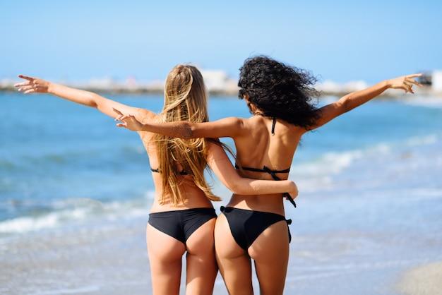 Achtermening van jonge vrouwen met mooie organismen in bikini die pret op een tropisch strand hebben. Gratis Foto