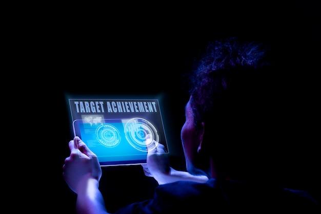 Achtermening van mannelijke handen die tablet met de tekst van de doelvoltooiing op het scherm houden Premium Foto