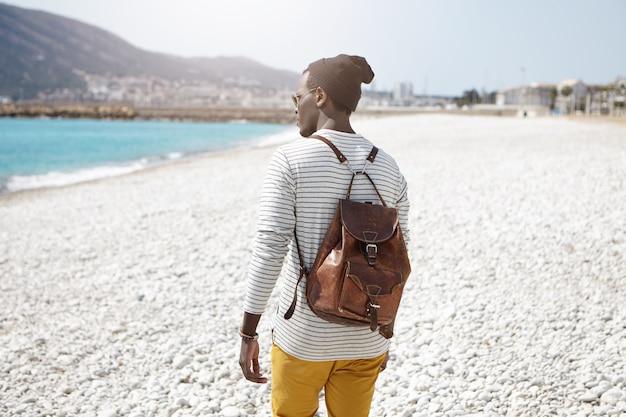 Achtermening van modieuze zwarte mannelijke student die bruine leerrugzak en modieuze hoed op warme de lentedag dragen die aardige gang op strand hebben Gratis Foto