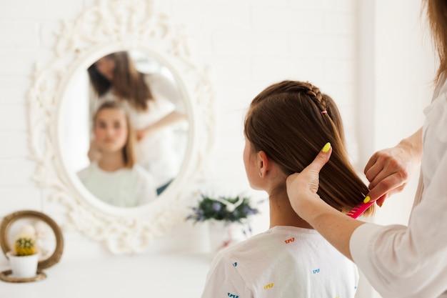 Achtermening van moeder die het haar van haar dochter thuis binden Gratis Foto