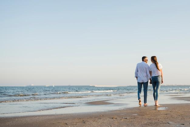 Achtermening van paar die op zandig strand lopen Gratis Foto