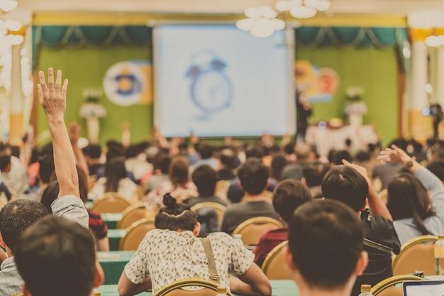 Achtermening van publiek die hand tonen om de vraag van spreker op het stadium te beantwoorden Premium Foto