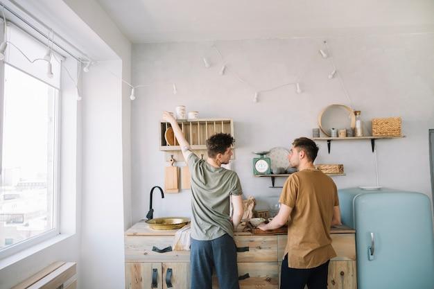 Achtermening van vrienden die voedsel in binnenlandse keuken voorbereiden Gratis Foto
