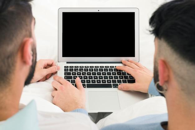 Achtermening van vrolijk paar die de digitale tablet op bureau gebruiken Gratis Foto