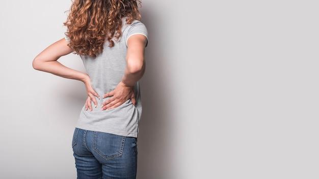 Achtermening van vrouw die rugpijn hebben tegen grijze achtergrond Gratis Foto