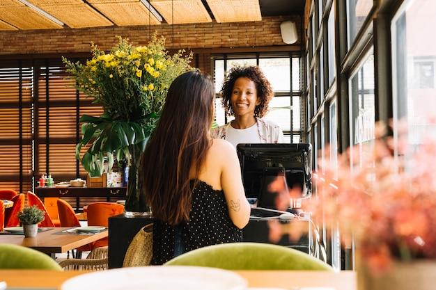 Achtermeningsvrouw die zich voor jonge vrouwelijke kassier bevinden die bij de kassa in koffie werken Gratis Foto