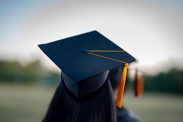 Achterportret van afgestudeerd met een zwarte hoed op. Premium Foto