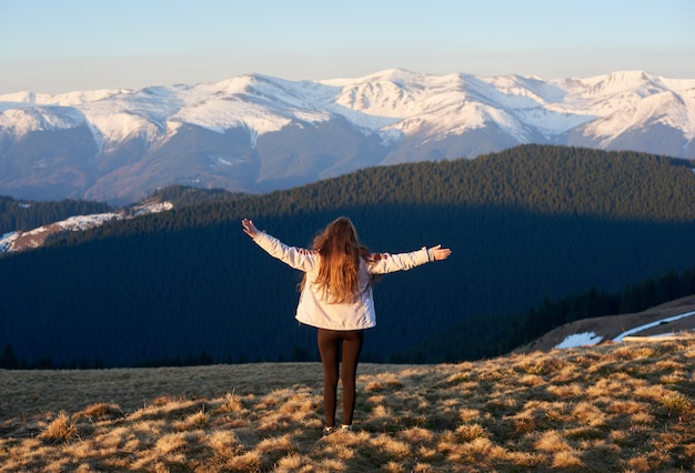 Achteruitkijkschot van een avontuurlijke meisjeswandelaar die zich bovenop de berg met haar uitgespreide wapens bevindt Premium Foto