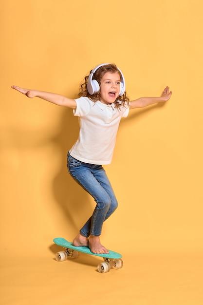 Actief en gelukkig meisje met krullend haar, koptelefoon plezier met cent board Premium Foto