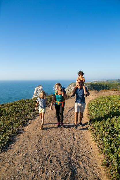 Actieve familie paar en kinderen wandelen langs zee, wandelen op pad. jongen rijden op vaders nek. volledige lengte. natuur en recreatie concept Gratis Foto