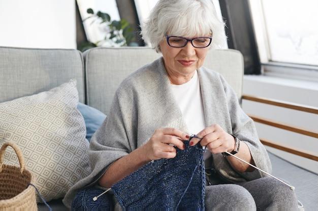 Actieve getalenteerde blanke vrouw op pensionering dag binnenshuis, warme kleren breien voor kleinkinderen, zittend op de bank in gezellig interieur, glimlachend. handwerk, handwerk en hobbyconcept Gratis Foto