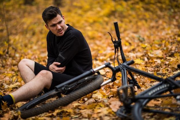 Actieve jonge mensenholding door zijn gekwetste of gebroken handen terwijl het liggen op de herfst bosweg door zijn fiets Gratis Foto