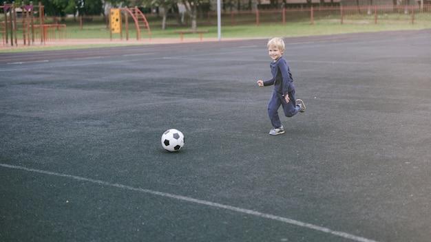 Actieve levensstijl in een moderne stad - kleine jongen die met een voetbal in het stadion speelt Premium Foto