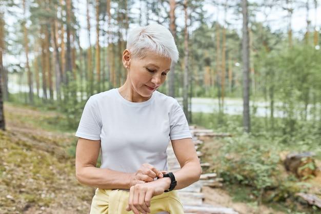 Actieve rijpe vrouw met kort blond haar poseren buitenshuis, klaar voor joggen oefening, slimme horloge instellen, hartslag en pols bijhouden. Gratis Foto