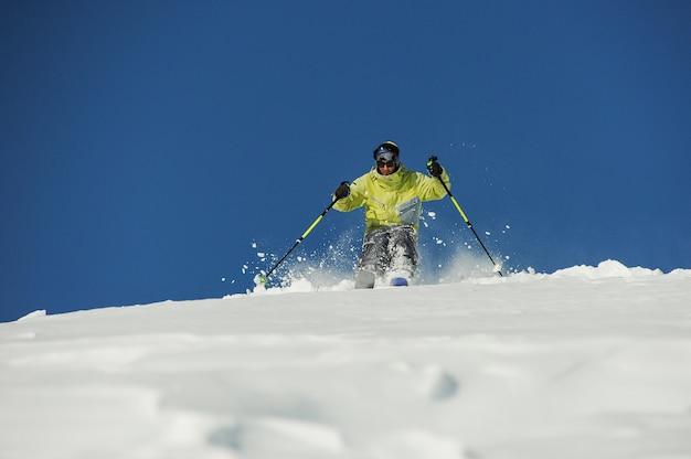 Actieve skiër in gele sportkleding rijden de helling af in georgië, gudauri Premium Foto