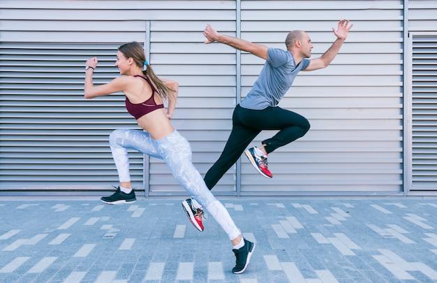 Actieve sportieve jonge mannelijke en vrouwelijke atleet die en in lucht lopen springen Gratis Foto