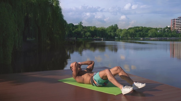 Actieve sterke man doet abs oefeningen op houten pier van het meer Premium Foto