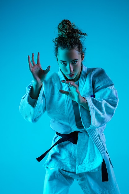 Actieve training. professionele vrouwelijke judoist in witte judo kimono oefenen en trainen geïsoleerd op blauwe neoned studio achtergrond. Gratis Foto