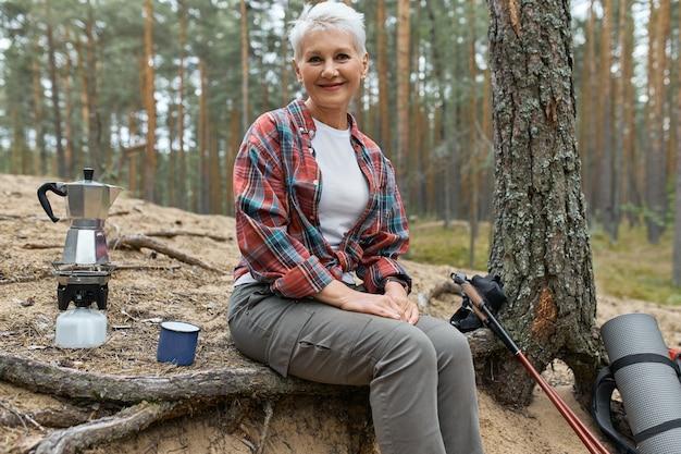 Actieve vrolijke vrouw van middelbare leeftijd zittend onder de boom met kampeerspullen kokend water voor thee op gasfornuisbrander, met een kleine pauze tijdens lange afstandstochten. mensen, avontuur, reizen en wandelen Gratis Foto