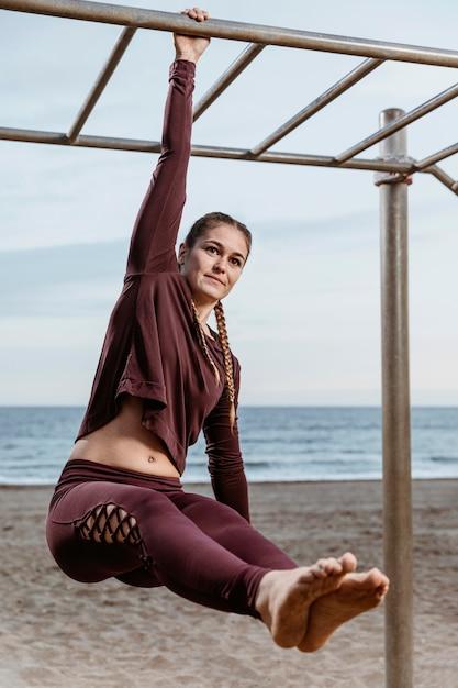 Actieve vrouw die buiten aan het strand uitoefent Gratis Foto