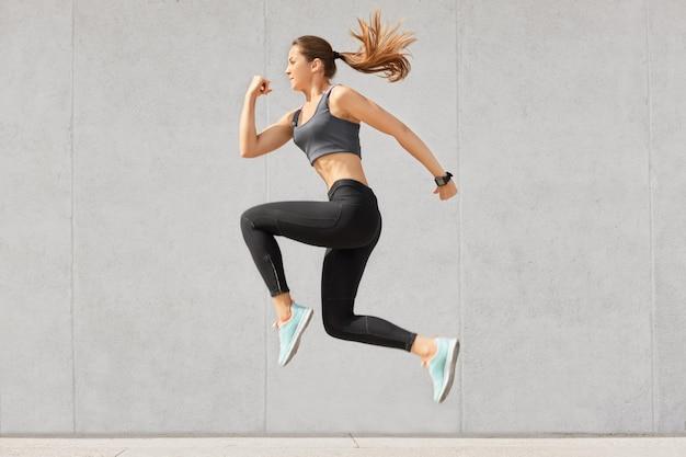 Actieve vrouw die vol energie is, hoog in de lucht springt, sportkleding draagt, zich voorbereidt op sportwedstrijden Gratis Foto