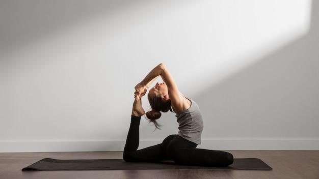 Actieve vrouw thuis beoefenen van yoga Gratis Foto