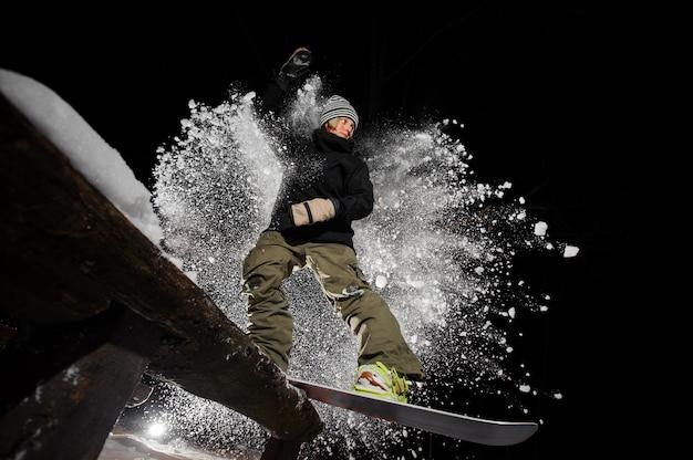 Actieve vrouwelijke snowboarder die onderaan de berghelling berijdt bij nacht Premium Foto