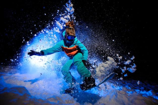 Actieve vrouwelijke snowboarder gekleed in een oranje en blauwe sportkleding die op de sneeuw springt Premium Foto