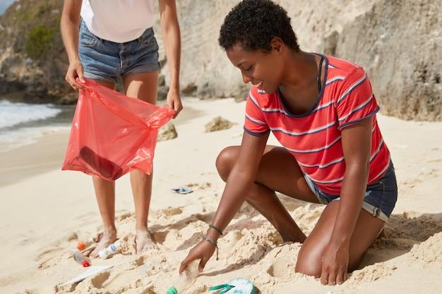 Actieve vrouwtjes maken het strand schoon van afval Gratis Foto