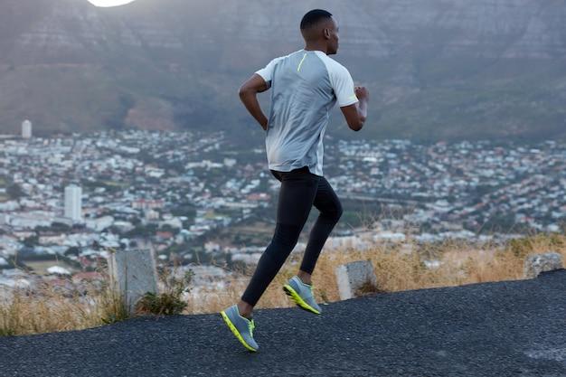 Actieweergave van mannelijke jogger beslaat lange afstand, gekleed in een casual legging en t-shirt, poseert over de bergen op de weg, heeft sportschoenen, komt op adem tijdens cardiotraining. beweging, snelheid concept Gratis Foto