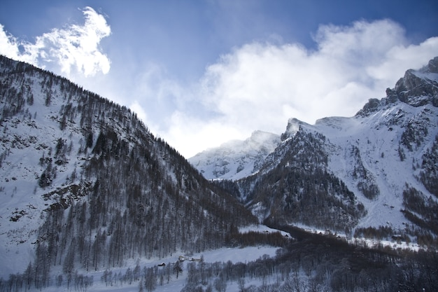 Adembenemend landschap van de met sneeuw bedekte bergen onder een schilderachtige bewolkte hemel Gratis Foto