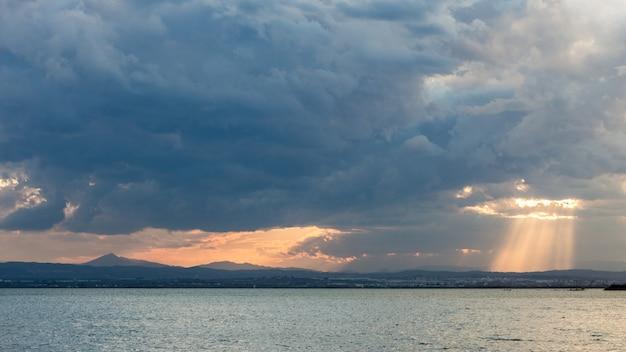 Adembenemend landschap van de zonsondergang die door wolken boven de vredige zee schijnt Gratis Foto