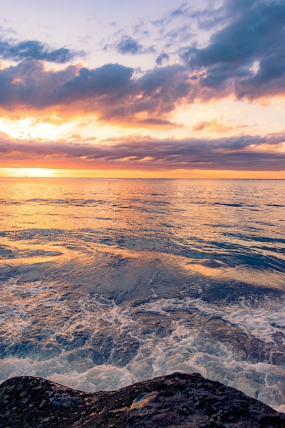 Adembenemend landschap van een rotsachtig strand op een prachtige zonsondergang op de achtergrond Gratis Foto