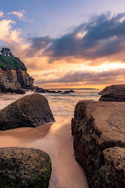 Adembenemend landschap van een rotsachtig strand op een prachtige zonsondergang Gratis Foto