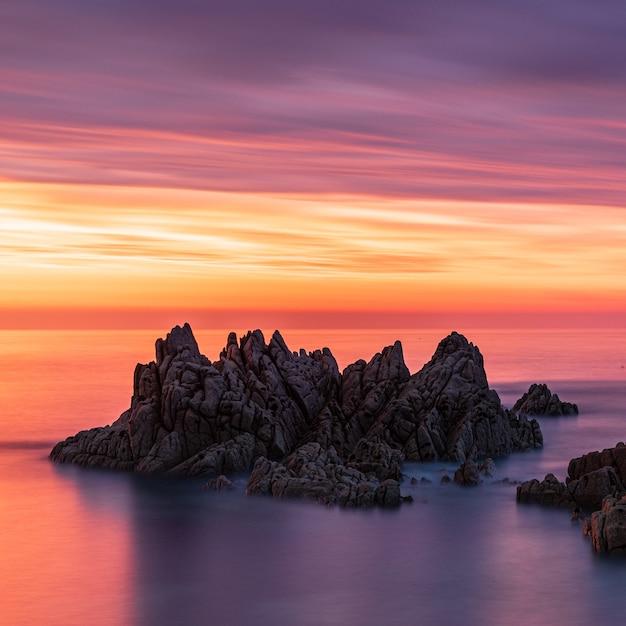 Adembenemend landschap van zeestapels tijdens zonsondergang onder de kleurrijke lucht in guernsey Gratis Foto