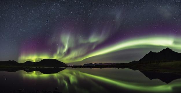 Adembenemend schot van wind van kleuren die in de overzees in lofoten, noorwegen nadenken Gratis Foto