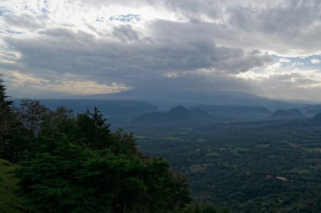 Adembenemend uitzicht op bergen en groene bossen met prachtige wolken Gratis Foto
