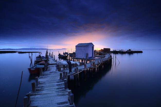 Adembenemend uitzicht op een houten pier en een huisje over de kalme oceaan bij schemering Gratis Foto