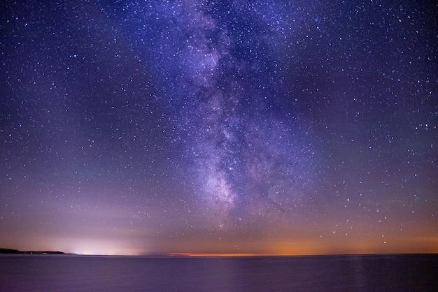 Adembenemende opname van de zee onder een donkere en paarse lucht vol sterren Gratis Foto