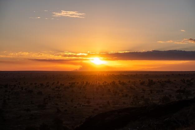 Adembenemende zonsondergang in de kleurrijke lucht boven een woestijn in tsavo west, kenia, kilimanjaro Gratis Foto