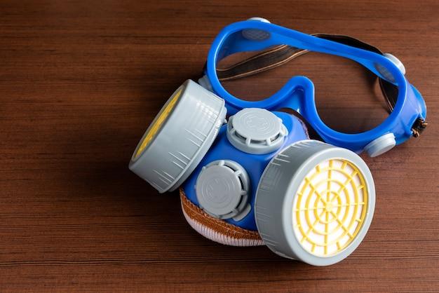 Ademhalingsmasker, stofmasker en veiligheidsmasker voor chemische industrie op houten achtergrond. Premium Foto