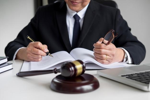 Advocaat hand schrijft het document in de rechtbank (gerechtigheid, wet) met klinkende blok Premium Foto