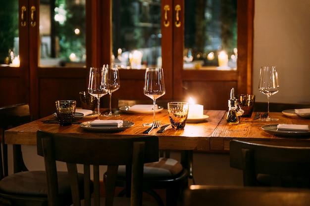 Afbeelding bijsnijden van romantische fijne eettafel met bestek, borden, wijnglazen, servetten en luiers op tafel. lichtbron van kaarslicht. Premium Foto