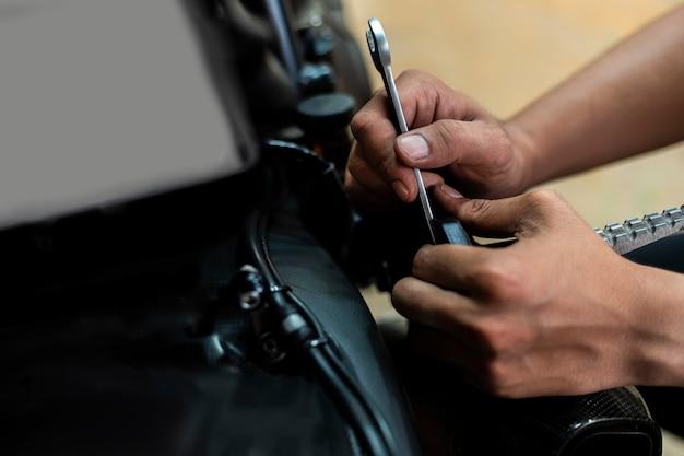 Afbeelding is close-up, auto-reparatie repareert een motorfiets gebruik een moersleutel en een schroevendraaier om te werken. Premium Foto