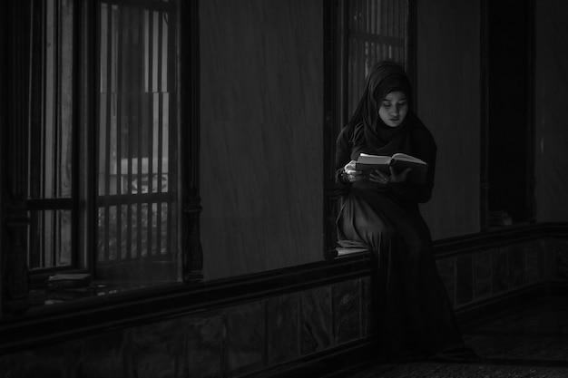Afbeelding is zwart en wit. moslimvrouwen die zwarte shirts dragen. gebed volgens de principes van de islam. Premium Foto
