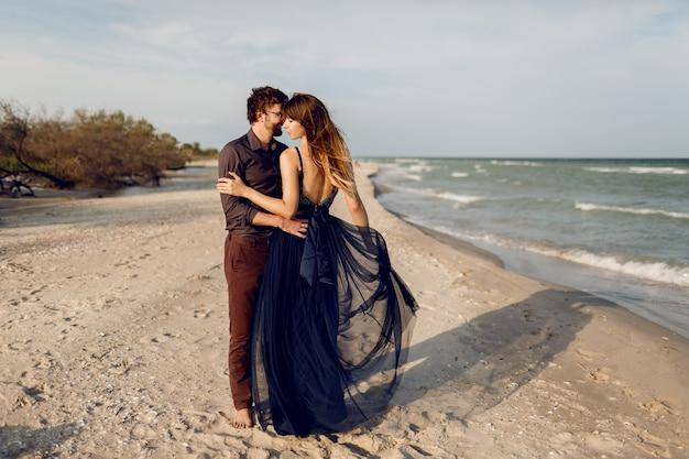 Afbeelding op volledige hoogte van romantische paar omhelzing op het strand van de avond in de buurt van de oceaan. prachtige vrouw in blauwe lange jurk knuffelen haar vriendje met tederheid. huwelijksreis. Gratis Foto