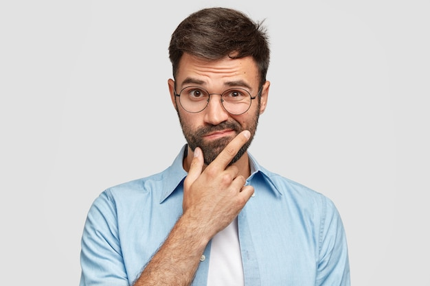 Afbeelding van aarzelende ongeschoren europese man met dikke baard, kin vasthoudt, lippen tuit met clueless uitdrukkingen Gratis Foto
